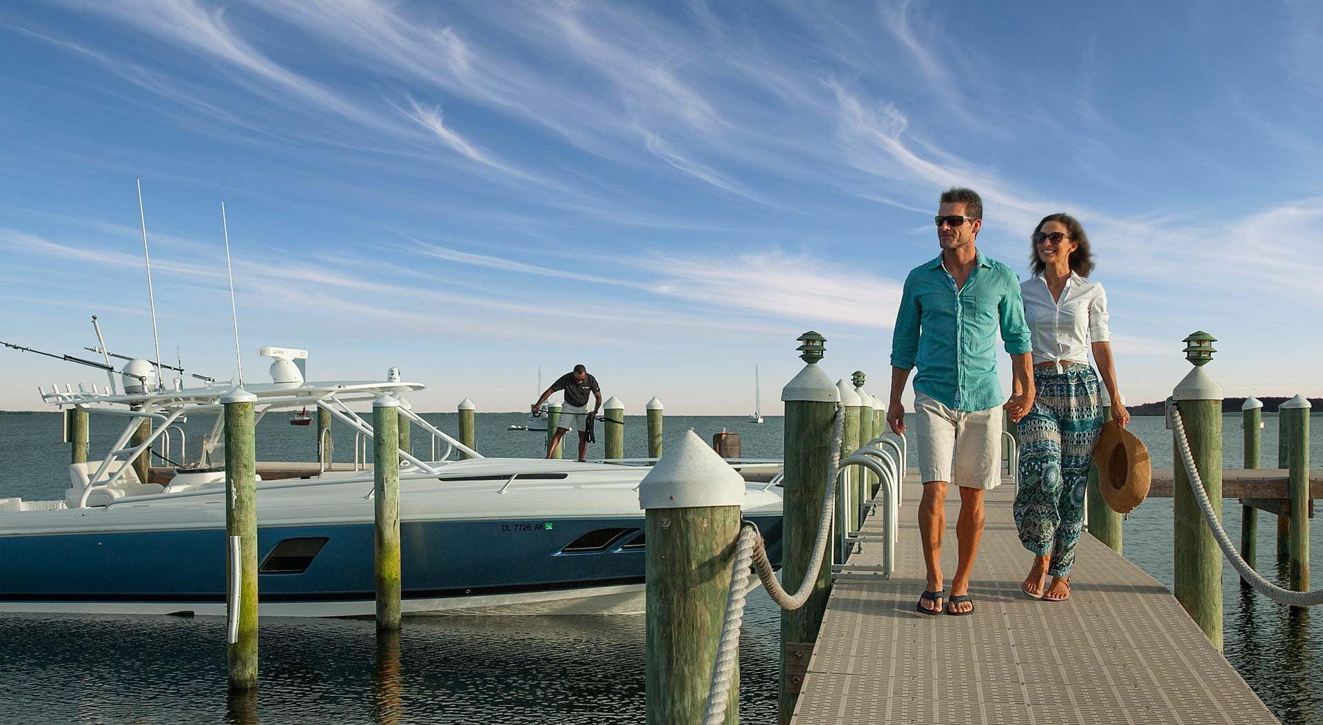 couple walking on dock away from boat towards shore