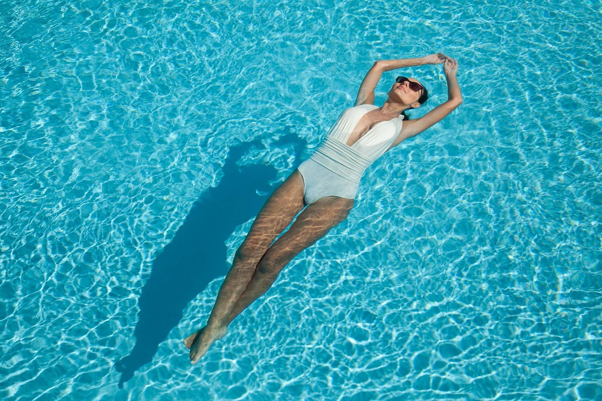woman in one piece white bathing suit floating in pool