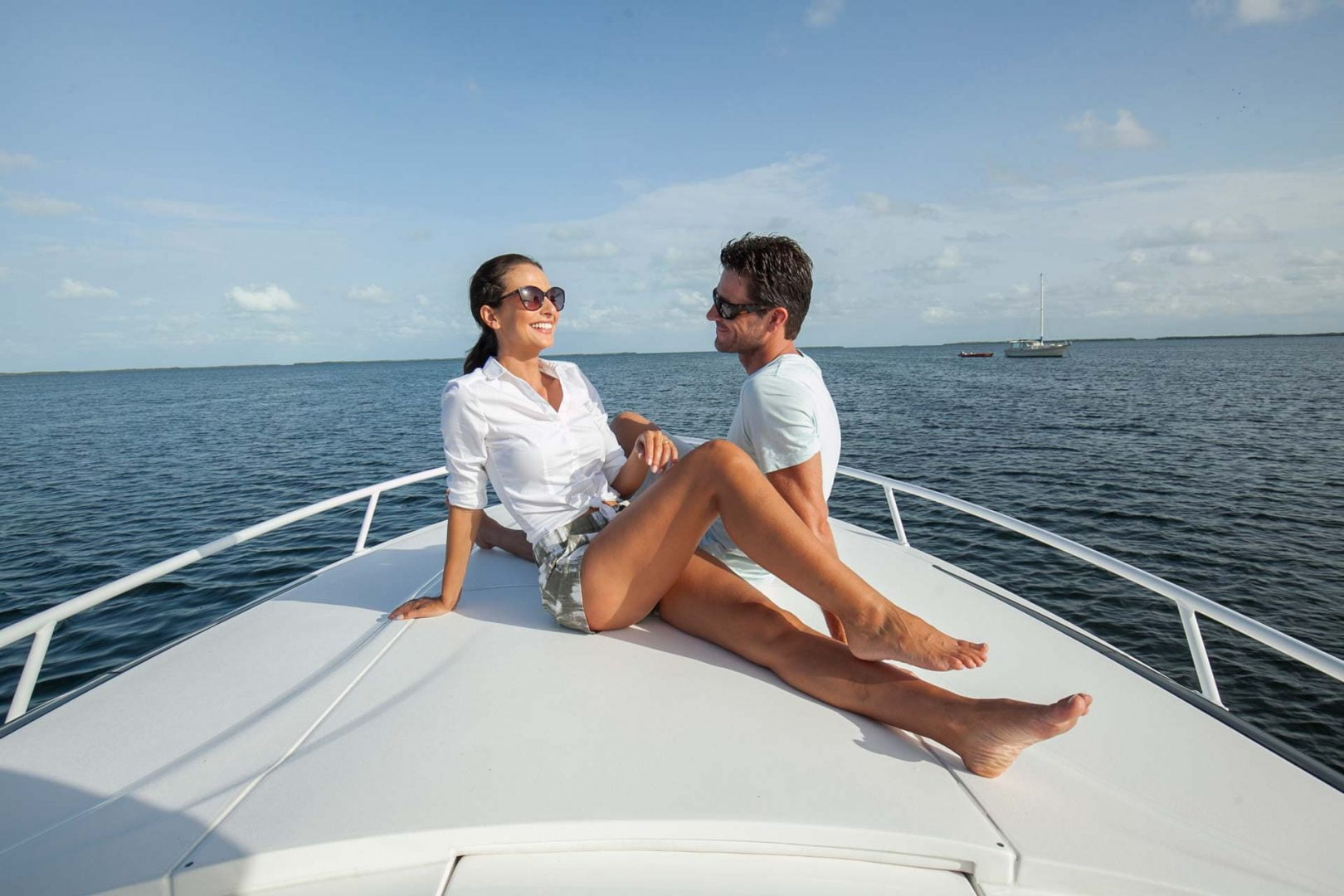 man and woman lounging on bow of yacht