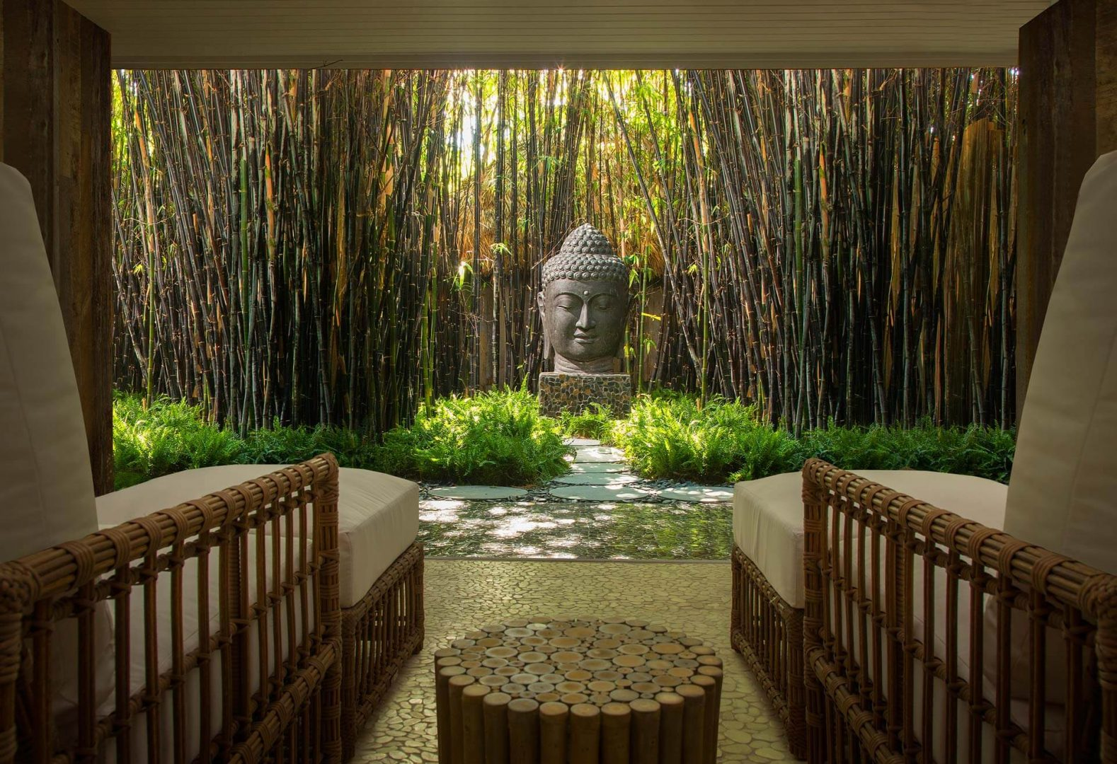 Bamboo garden with Buddha head and two chairs