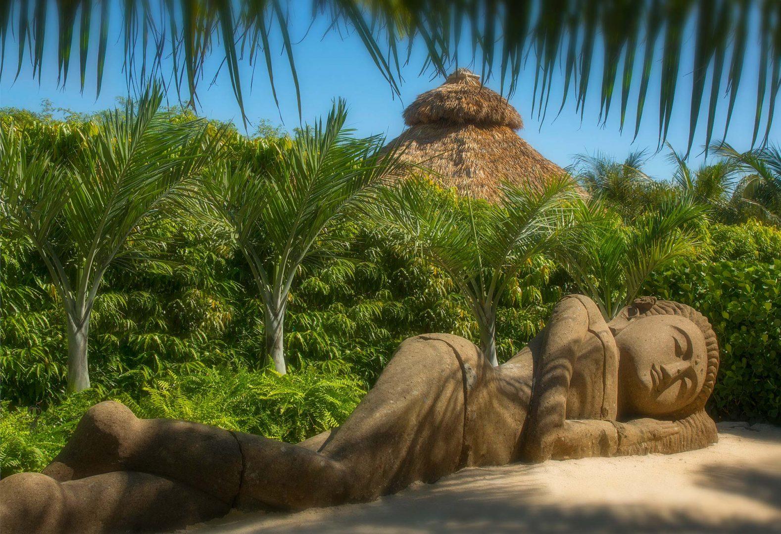 large sleeping statue on a sandy beach