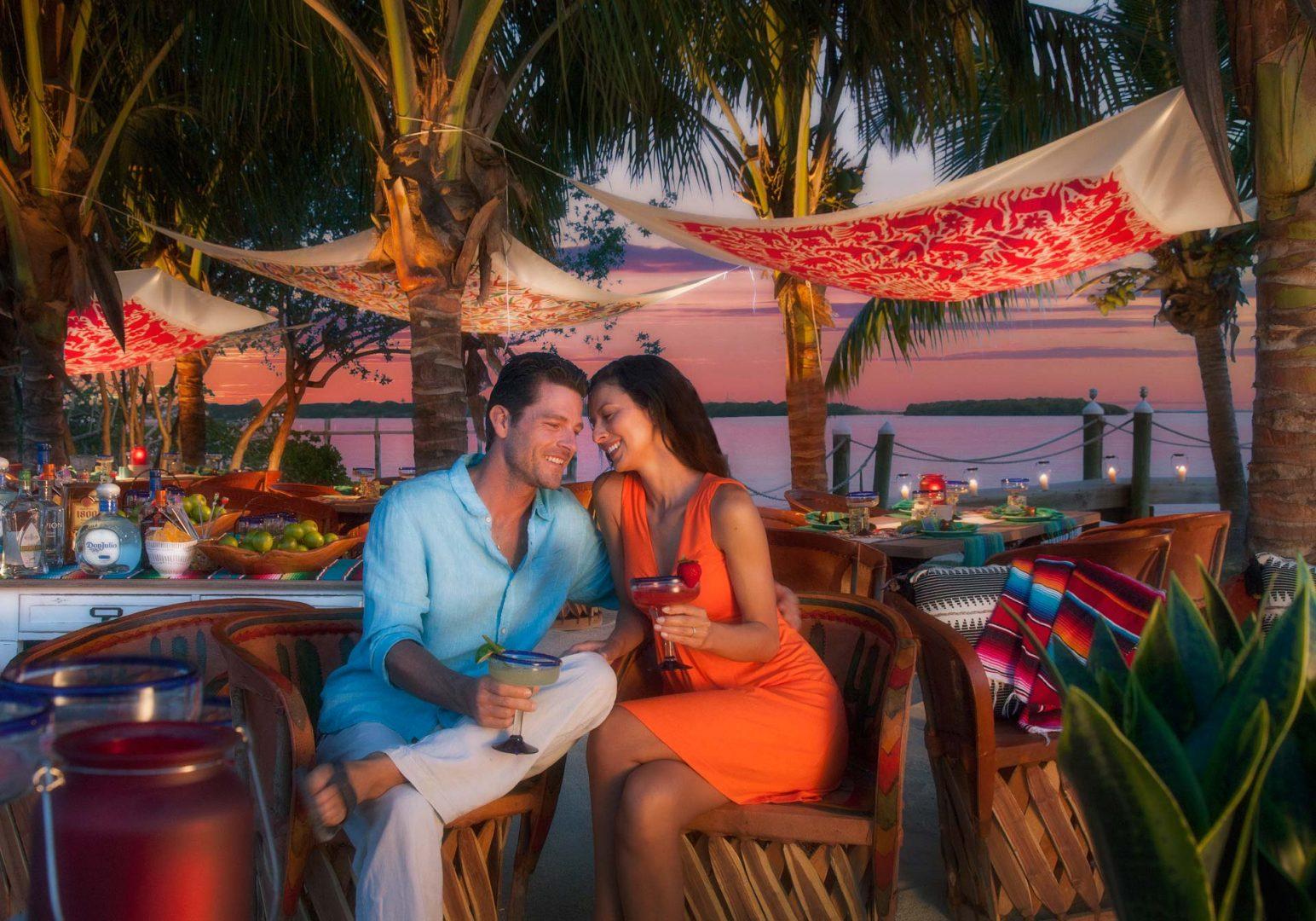 couple sitting by water enjoying margaritas at sunset