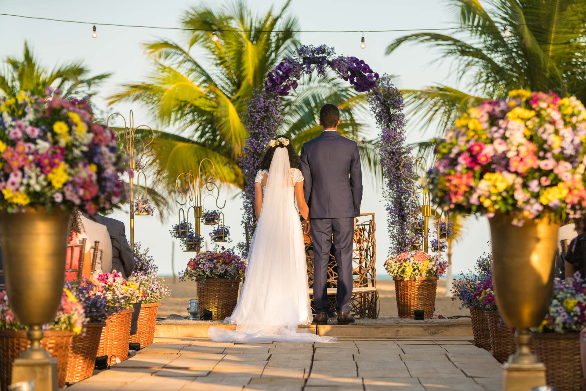 bride and groom facing away from camera on beach under floral arch