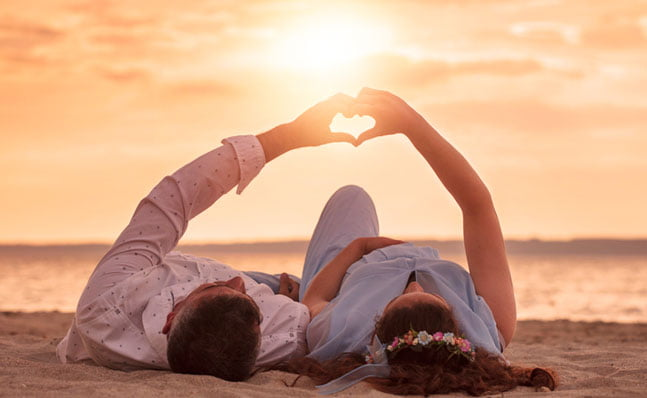 couple laying on beach at sunset making a heart with their hands