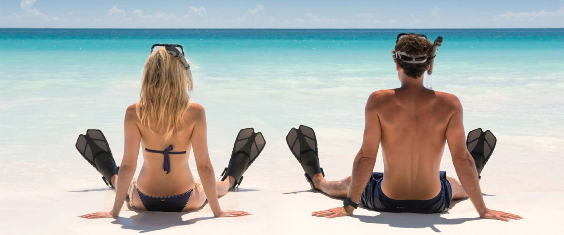 male and female snorklers sitting on beach looking at water